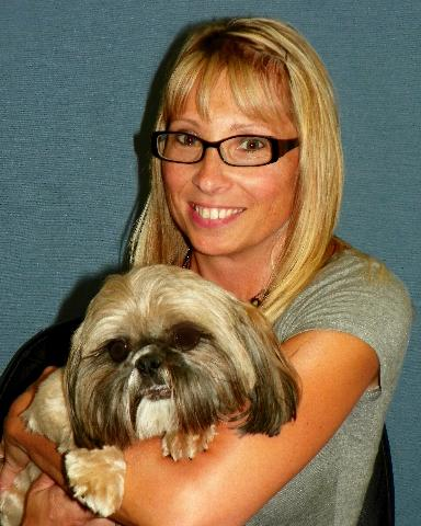 Team member Carrie with a small white and grey dog